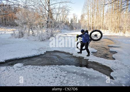 Cycliste traverse l'eau libre de Campbell Creek tout en transportant un VTT dans la neige loin au nord de Bicentennial Park près d'Anchorage, Alaska Banque D'Images