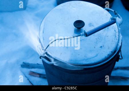 Mehtanol-flamme alimentée chauffe une casserole d'eau pour faire fondre la neige pour un attelage de chiens, Gates Banque D'Images