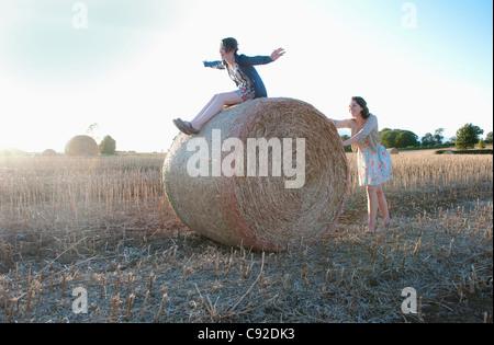 Les filles jouant sur hay bale in field Banque D'Images
