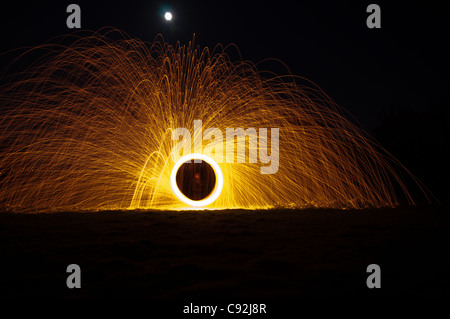 Filature de laine d'acier, créant de magnifiques traînées circulaire de lumière dorée de brûler de l'intérieur laine Banque D'Images