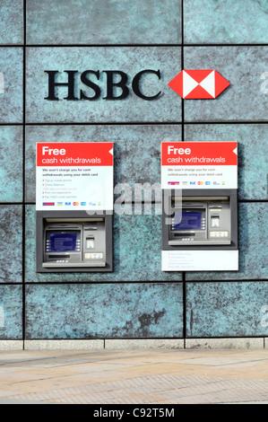 Deux distributeurs de billets ATM de la banque HSBC de retirer de l'argent dans un trou dans le mur de la banque ci-dessous logo banque signe et dans City of London England UK