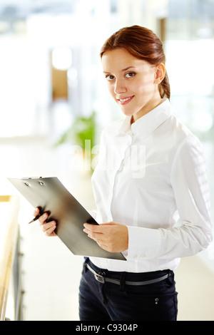 Jeune femme d'affaires avec presse-papiers looking at camera and smiling Banque D'Images