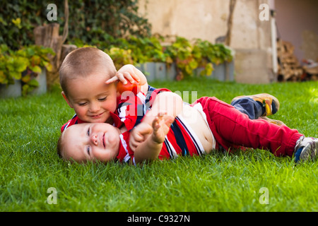 Cute little brothers jouant dans l'herbe. Banque D'Images