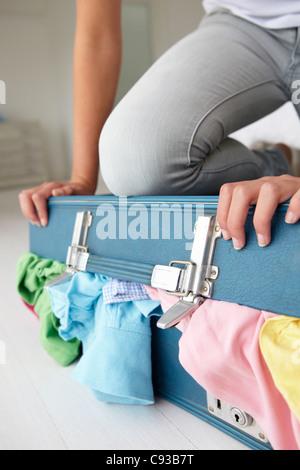 Adolescente mal à fermer suitcase Banque D'Images