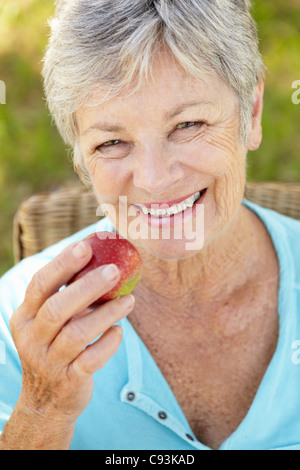 Senior woman eating apple outdoors Banque D'Images