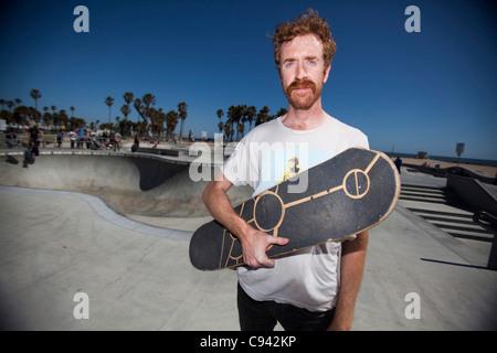 Man Holding Skateboard dans Skate Park Banque D'Images
