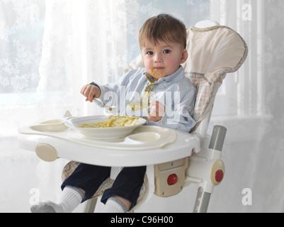 Un an et demi ans garçon assis sur une chaise haute et de manger la soupe avec une cuillère, déversant sur son T Banque D'Images