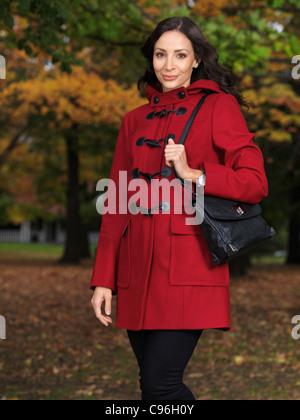 Belle jeune femme portant un manteau rouge debout sur une rue de ville en automne