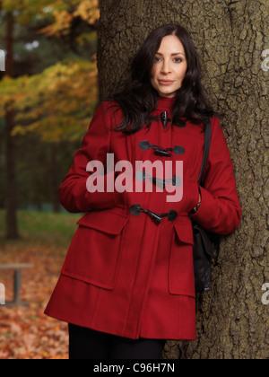Portrait of a beautiful smiling woman in red coat appuyé contre un arbre en automne park