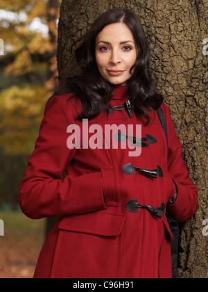 Portrait d'une belle femme en robe rouge à la mode appuyé contre un arbre