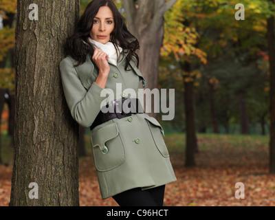 À la mode pour l'automne, la belle jeune femme dans un manteau vert, appuyé contre un arbre dans un parc.