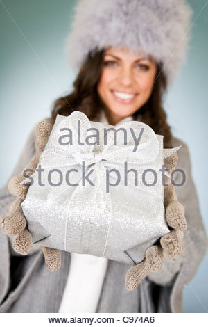 A young woman holding a Christmas present Banque D'Images