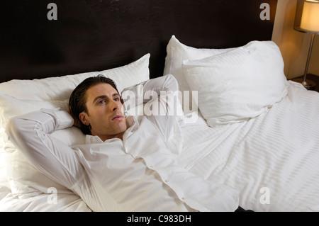 Jeune homme allongé seul dans le lit avec une expression Banque D'Images