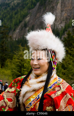 La femme chinoise traditionnelle tibétaine en tourisme costume national / robe, with fur hat & manches longues. Banque D'Images