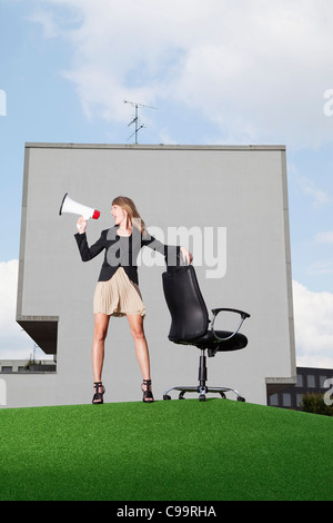 Germany, Bavaria, Munich, femme d'meghaphone crier à travers la pelouse dans