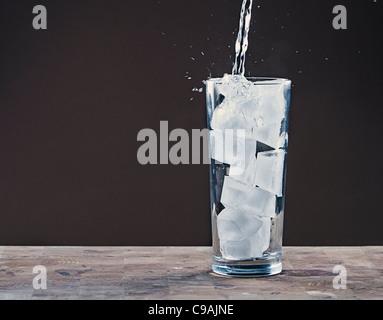 Verser de l'eau dans un verre rempli de cubes de glace Banque D'Images