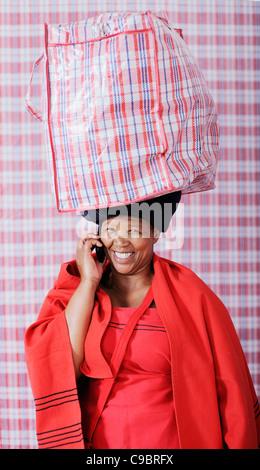 Femme en tenue traditionnelle sac de transport sur l'utilisation de téléphone mobile, Cape Town, Western Cape Province, Banque D'Images