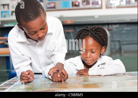 Garçon et fille l'observation de la carte du monde en classe, Johannesburg, la Province de Gauteng, Afrique du Sud Banque D'Images