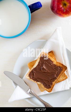 Petit déjeuner avec chocolat à tartiner sur des toasts et du lait Banque D'Images