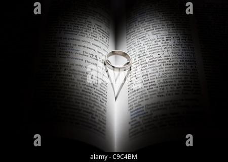 Avec bague en or en forme d'ombre hart sur les pages d'un livre Banque D'Images