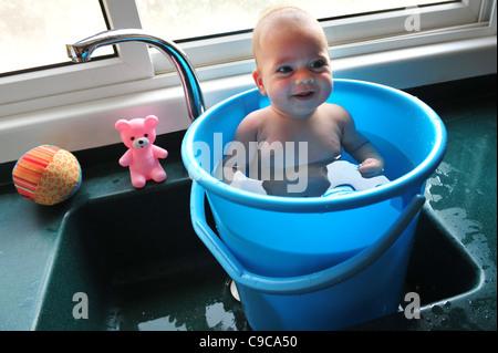 Un bébé dans un seau bleu refroidit dans la chaleur de l'été Banque D'Images