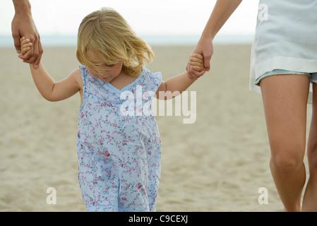 Petite fille qui marche main dans la main avec les parents à la plage, cropped Banque D'Images