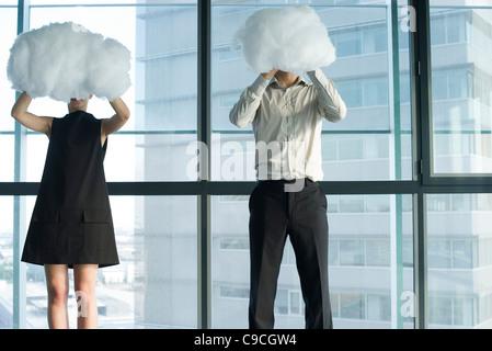 Businessman and businesswoman se cachant derrière les nuages Banque D'Images