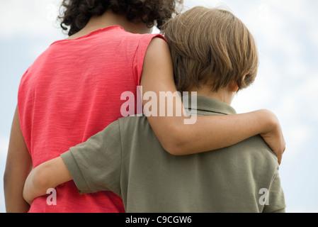Les jeunes frères enlacés, vue arrière Banque D'Images