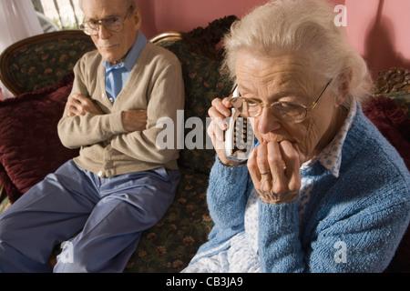 Hauts femme parle au téléphone sans fil tout en grognon man watches Banque D'Images