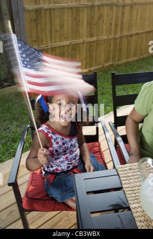 Petite fille à 4 juillet barbecue waving American flag Banque D'Images