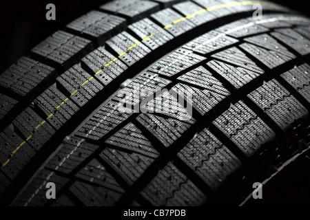 Partie de tout nouveau pneu de voiture. Shallow DOF. Arrière-plan arrière noir. Banque D'Images