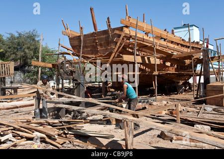 Les hommes La construction d'un bateau de pêche traditionnel. Vanakbara chantier naval. Diu. Territoires de l'Union Banque D'Images