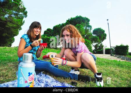 Les adolescentes les pique-niques in rural field Banque D'Images