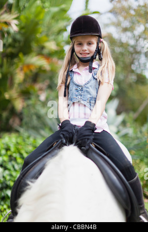 Smiling girl riding horse in park Banque D'Images
