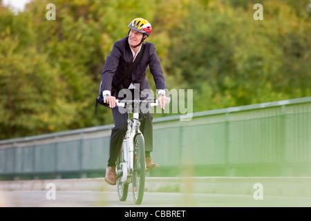 Businessman riding bicycle on bridge