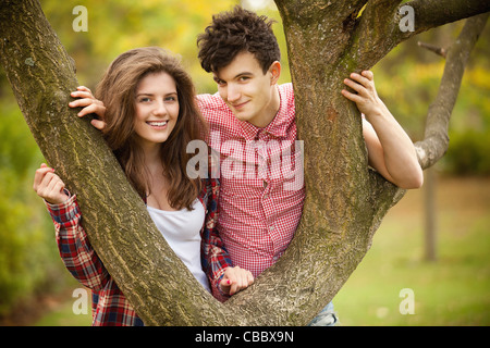 Teenage couple climbing in park Banque D'Images