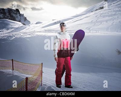Femme portant des neiges on snowy slope Banque D'Images