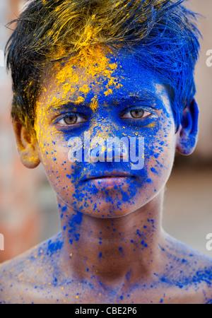 Jeune Indien garçon couvert de pigments en poudre de couleur Banque D'Images