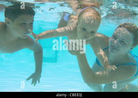 Famille sous-marine en piscine. L'enseignement de la mère de ses enfants Banque D'Images