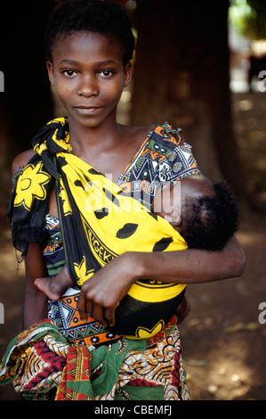 Izinga, Tanzanie. Femme portant des vêtements en coton imprimé portant son bébé lié à elle dans un chiffon. Banque D'Images
