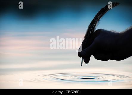Main tenant au-dessus de l'eau de la douille avec silhouette d'ondulation Banque D'Images