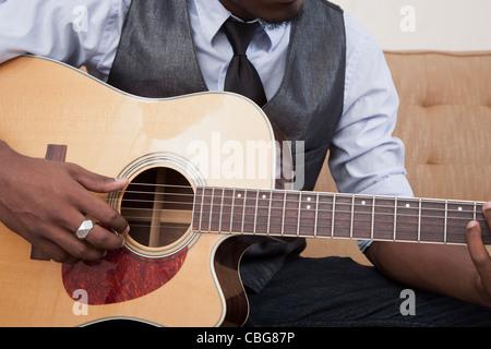 Un jeune homme jouant de la guitare acoustique, l'accent sur l'abdomen Banque D'Images