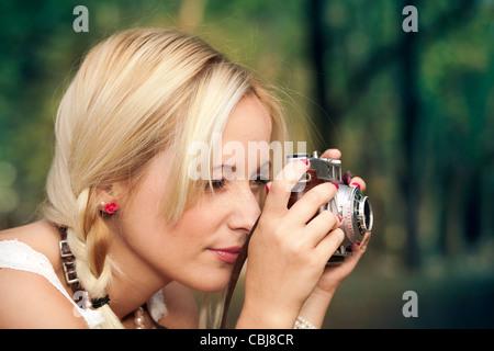 Belle jeune fille pour prendre des photos avec un appareil photo vintage ancien Banque D'Images