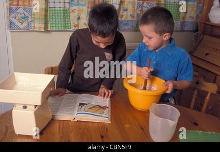 Deux jeunes garçons faire des crêpes Banque D'Images