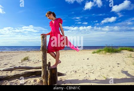 La jeune femme en robe rouge sur une plage. Banque D'Images
