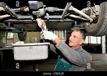 Le changement d'huile moteur mécanique. Banque D'Images