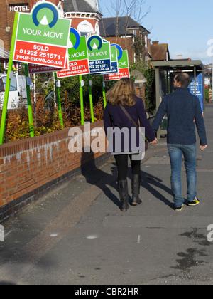 Jeune couple walking down road à la maison à vendre à vendre maison et signes sur une rue dans le centre de Exeter Banque D'Images