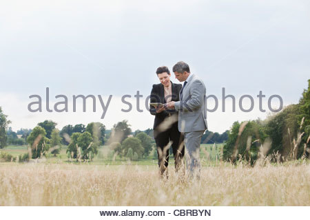 Business people using digital tablet outdoors Banque D'Images