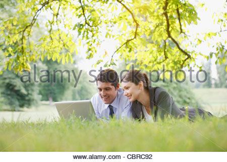 Les gens d'affaires laying in grass using laptop Banque D'Images