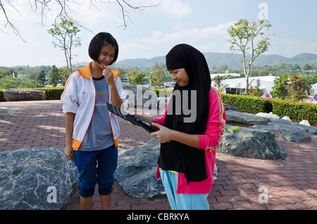 Musulmans thaïlandais Smiling teenage girl wearing long foulard noir regarde des photos sur son iPad avec ami dans Banque D'Images